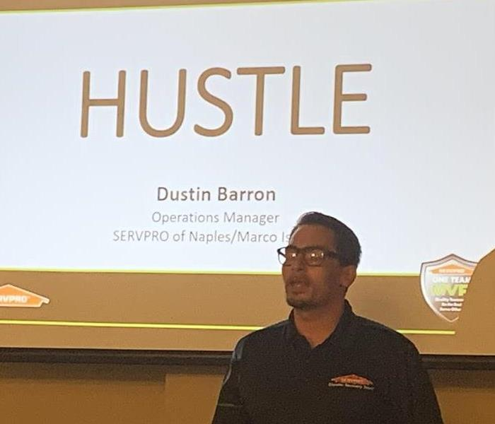 SERVPRO employee standing in front of a projection screen with the word Hustle on it.